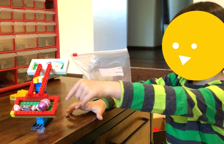 Kid playing with Lego balance scale